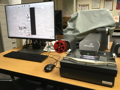 Microfilm machine with microfilm reel and computer monitor showing an old newspaper